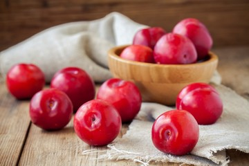 red plums in a bowl on an old rustic background