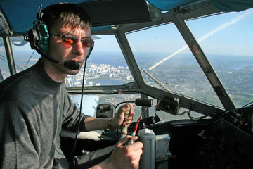 Young pilot in the cockpit aircraft during flight