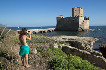 girl taking picture of torre astura castle