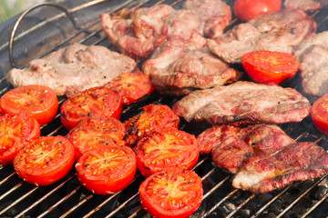 Pork steaks and tomatoes on the grill, garden barbecue party