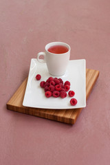 Raspberry drink on a wooden board and a pink background