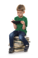 boy sitting on the books with tablet computer
