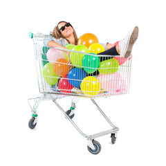 Girl with many balloons inside supermarket cart