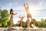 Fototapeta Group young  Friends Playing Volleyball On Beach