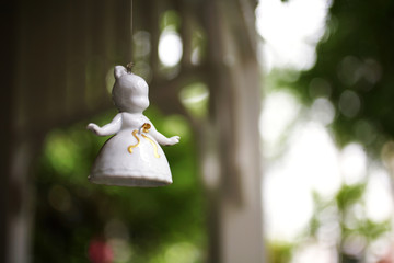 little angel ceramic doll in garden