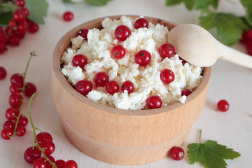 Cottage cheese and red currants in wooden bowl