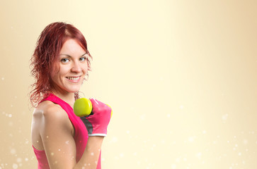 Redhead girl doing weightlifting over ocher background,