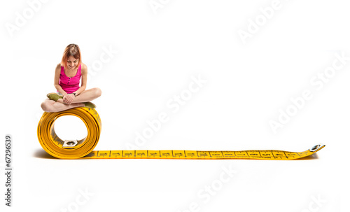 Young pretty girl looking down on tape measure