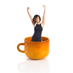Woman inside ceramic cup over white backgrpund