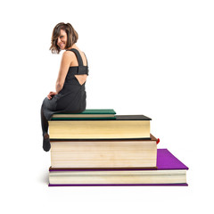 Woman on several books over white background
