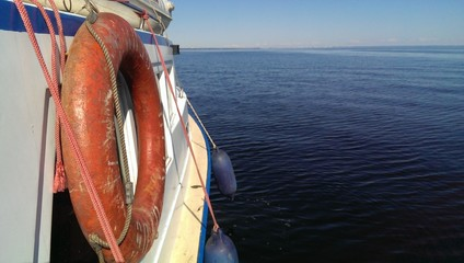 Sea trip, White boat hull with red safe buoy on board