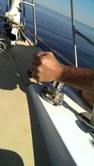 Male hand works with anchor winch on Small yacht