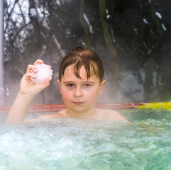 boy enjoys swimming in the warm outdoor pool with a snowball in