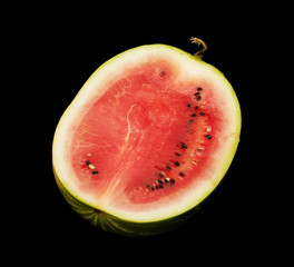 Half cut watermelon isolated on the dark background