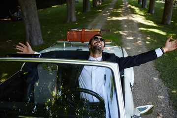 Rich elegance  man with arms raised sitting in cabriolet car