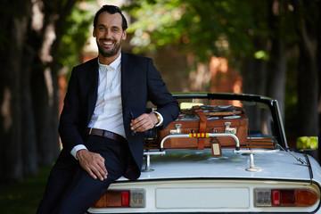 Elegance successful man in tuxedo leaning at luxury car