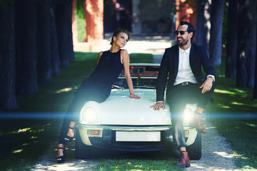 Rich and elegant couple leaning at their classic luxury car