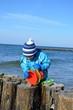 Kind mit Eimer spielt am Meer im Winter