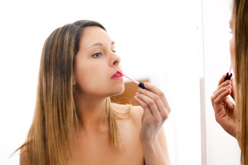Woman applying red lipstick at the mirror