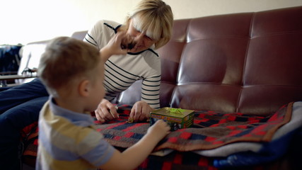 Grandmother and grandson playing with toy animals at home