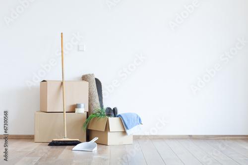 Umzugskartons mit Schaufel und Besen vor einer weißen Wand - 67300568
