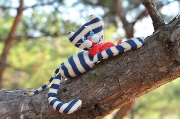 Funny toy cat laying on a pine stem