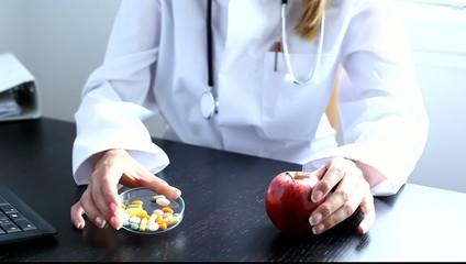 Ärztin zeigt Apfel und Pillen