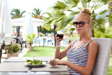 Красивая девушка с бокалом вина в кафе