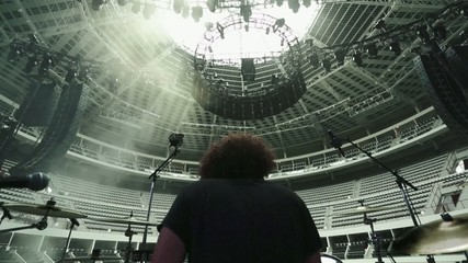Man playing drums at empty Coliseum.  Shot taken from behind him