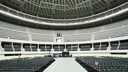 A white runway at empty coliseum before a show.