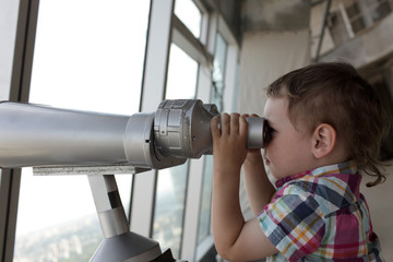 Boy looking through pay binoculars