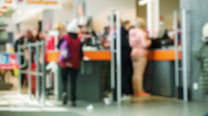 Customers in the supermarket paying at ther cashdesk, other come