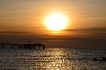 Angler auf Seebrücke bei Sonnenuntergang