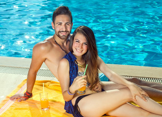 Beautiful happy couple relaxing at a pool.