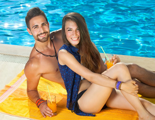 Smiling young couple enjoying a day at the pool.