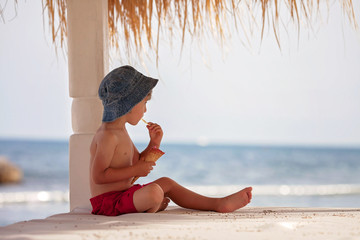 Cute shirtless boy, eating ice cream on the beach