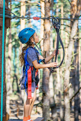 Little girl climbs on rope harness