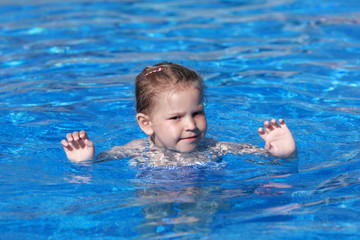 Happy little girl swims in the resort pool