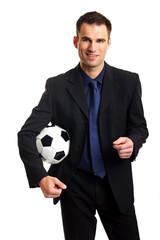 Handsome businessman in suit holds a soccer ball