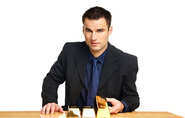 Handsome businessman in suit shows with his hands gold brick