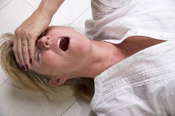 Woman laying on the floor with mouth open