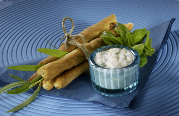 Sticks with feta cheese, tied with string, white dip, herbs