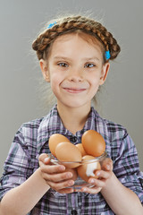 Little girl with chicken eggs