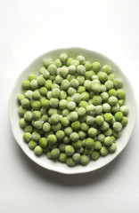 White plate of frozen green peas frozen balls