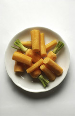 White plate of peeled orange carrots green leaves