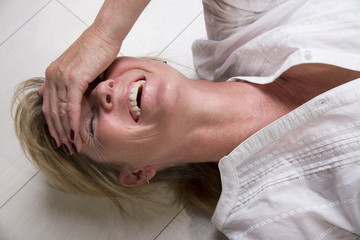 Woman laying on the floor with mouth open laughing