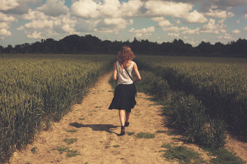 Young woman walking in a wheat field