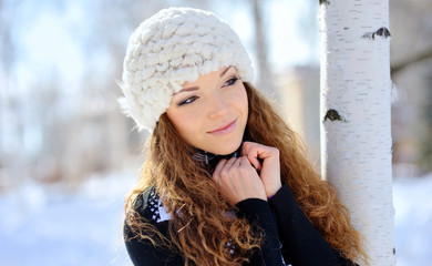 beautiful brunette in a white hat standing near birch in winter