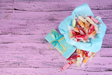 Tasty candies on paper with present on wooden background