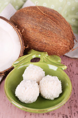 Broken coconut with candies on wooden background